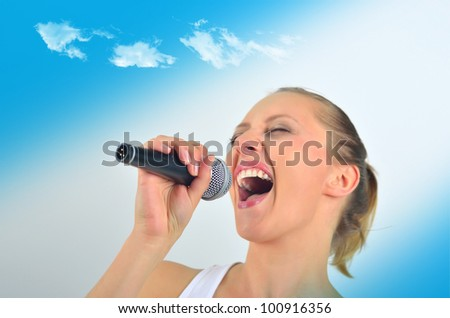 Sexy beautiful young woman singing with a microphone - stock photo