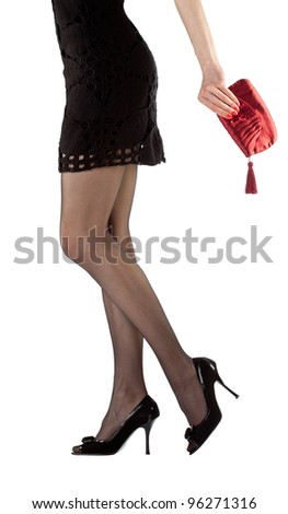 Sexy beautiful young woman wearing mini dress holding red handbag; closeup of hand and legs isolated on white - stock photo