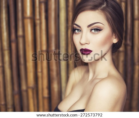 Sexy Beauty Girl with purple-red Lips. Provocative Make up. Luxury Woman with Green Eyes. Fashion Brunette Portrait on a bamboo (natural) background. Gorgeous Woman Face. Long Hair - stock photo