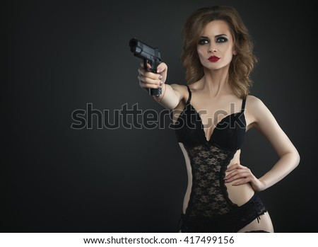 Sexy beauty young woman with gun in lingerie close up portrait - stock photo