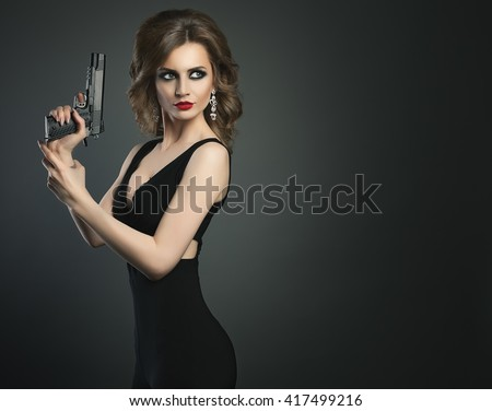 Sexy beauty young woman with gun on a dark bg portrait - stock photo