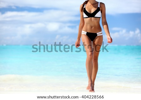 Sexy bikini body woman sun tanning relaxing on perfect tropical beach and turquoise ocean water. Unrecognizable model walking in fashion swimwear with smooth tanned skin and long lean legs. - stock photo