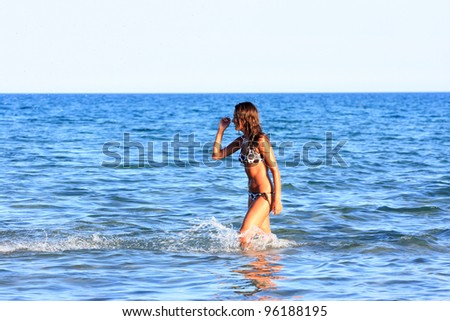 Sexy bikini model having fun in the ocean on vacation