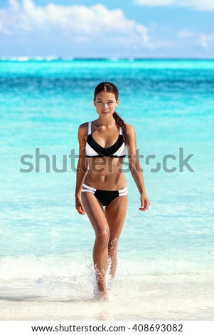 Sexy bikini woman on beach coming out of water walking relaxing on tropical getaway paradise. Young Asian ethnic model with slim weight loss body sunbathing in summer vacation travel. - stock photo
