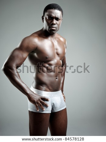 Sexy black model striking a serious pose in the studio - stock photo