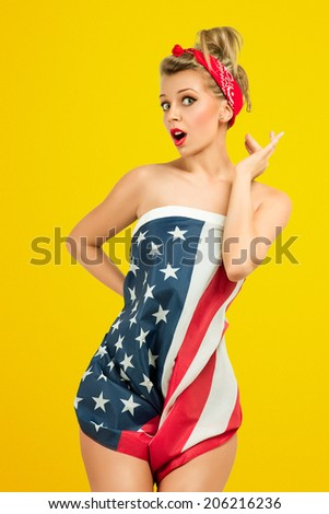 Sexy blond classic retro style pin-up model wrapped in american flag - stock photo