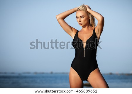 Sexy blond girl in black bikini posing on a beach