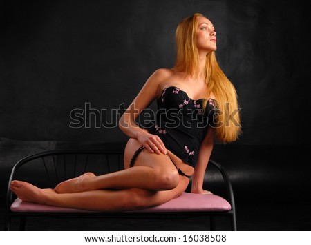 sexy blond girl in black bustier resting on a chair in a passionate pose