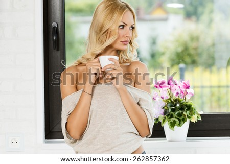 sexy blond girl informal dress with hot drink in cup looking outside of window . - stock photo
