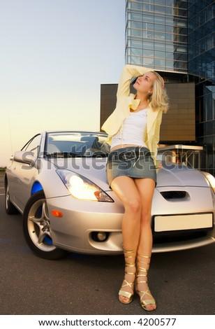 Sexy blond girl sits on modern sport car - stock photo