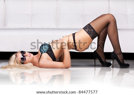 Sexy blond lady in dark underwear - stock photo