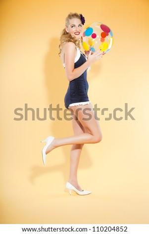 Sexy blond pin up girl wearing blue swimwear holding a colorful beach ball. Retro style. Fashion studio shot isolated on yellow background. - stock photo