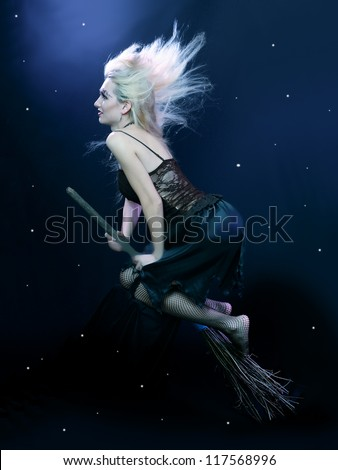 Sexy blond witch flying on broom on a dark sky with stars