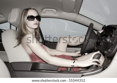 Sexy blond woman in a luxury car