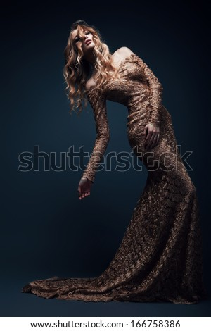 sexy blond woman in long gold dress - stock photo
