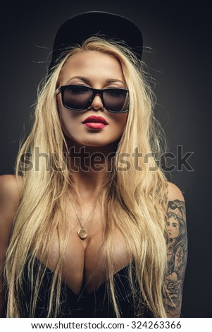 Sexy blond woman in sunglasses and cap posing over grey background.