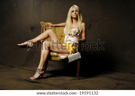 Sexy blond woman with makeup sitting on a chair - stock photo