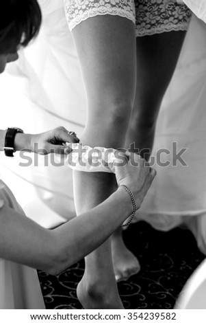 Sexy blonde caucasian  bride putting on white garter with bridesmaid closeup - stock photo