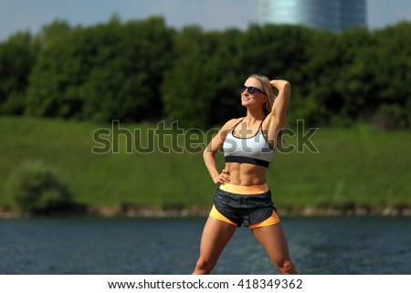 Sexy blonde fitness girl enjoying the sun at a river bank
