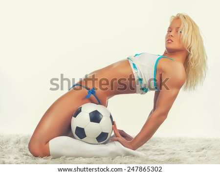Sexy blonde girl in seductive posion with a ball on furs - stock photo