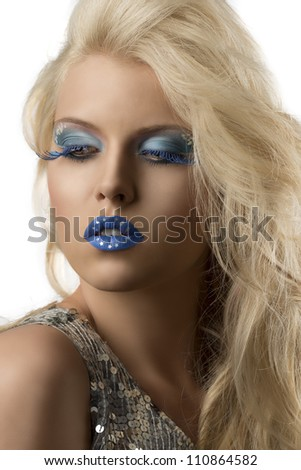 sexy blonde girl with blue creative make-up and glitter dress, she is slighlty turned of three quarters and looks down at right