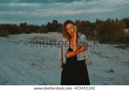 sexy blonde haired young woman posing in sands of desert lit by red setting sun light