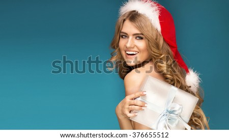 Sexy blonde happy girl posing in red santa claus hat, holding christmas gift. Blue background. - stock photo