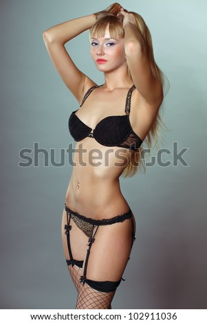 Sexy blonde in lingerie over dark background - stock photo