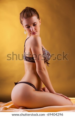 Sexy blonde in lingerie over yellow background - stock photo