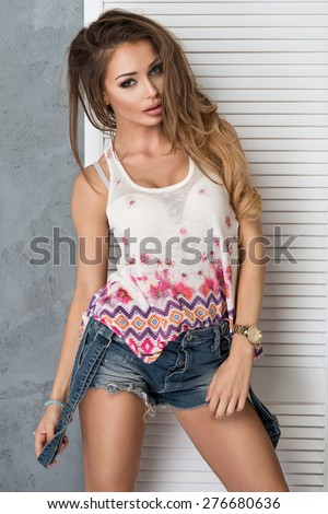 Sexy blonde lady in white shirt looking and jeans - stock photo