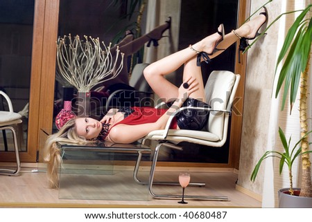 Sexy blonde lying on the glass table - stock photo