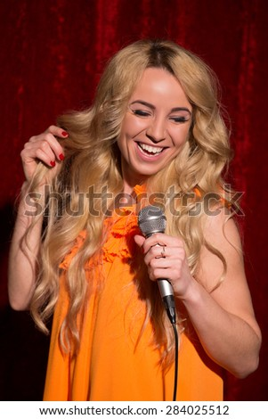 Sexy blonde singing and recording thousands of karaoke songs. Girl in orange dress laughing with microphone on red background. - stock photo