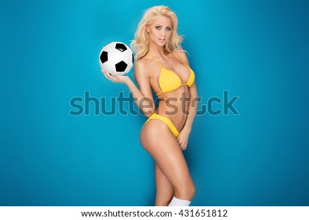 Sexy blonde woman as a soccer player. Fit body shape. - stock photo