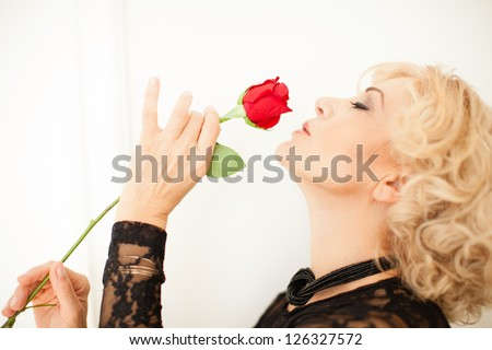 Sexy Blonde woman holding a rose and smelling it profile view - stock photo
