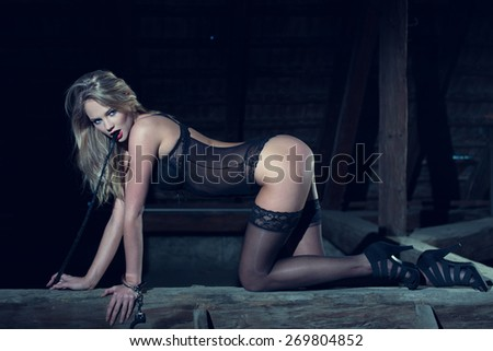 Sexy blonde woman in underwear kneeling on timber with whip, bdsm - stock photo