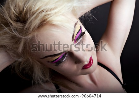 Sexy blonde woman in underwear with creative makeup on black background - stock photo