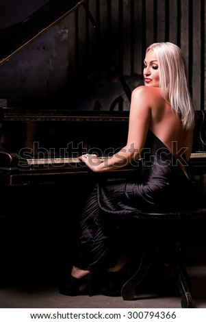sexy blonde woman sitting near piano Fashion studio portrait - stock photo