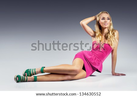 sexy blonde woman wearing pink dress and trendy wedge shoes sitting on the floor - stock photo