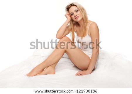 Sexy blonde woman with a beautiful smile sitting curled up on a bed in lingerie with copyspace - stock photo