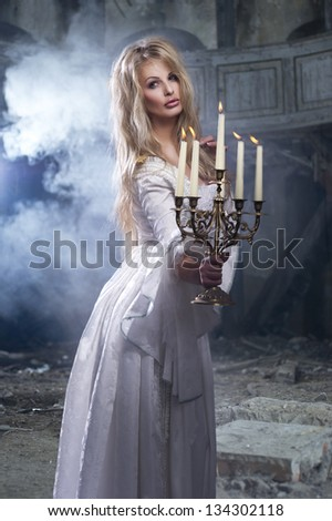 Sexy blonde woman with candlestick