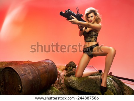 Sexy blonde woman with rifle - stock photo