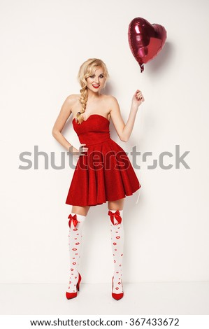 sexy blonde young woman in red dress and stockings holding heart-shaped balloon. Valentine's day - stock photo