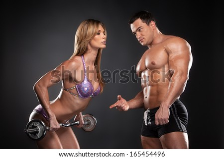 Sexy bodybuilder coach training beautiful fit blond woman. Standing together isolated over black background