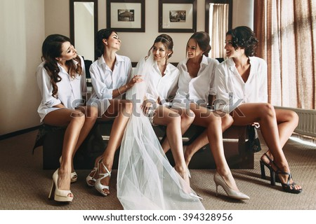Sexy bride & bridesmaids with long legs posing in shirts - stock photo
