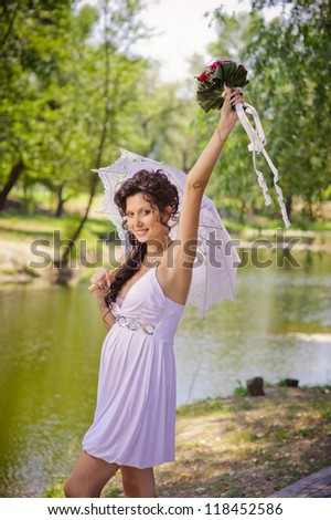 Sexy bride stands on the Lake shore in a park. wedding. Love story of happy couple. wedding dress and umbrella. Bridal wedding bouquet of flowers.