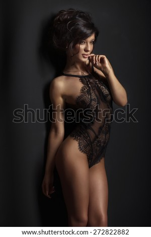 Sexy brunette beauty in black elegant lingerie posing. Girl with slim perfect body. - stock photo