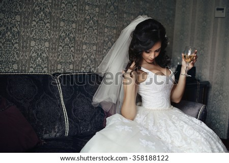Sexy brunette bride in white dress with champagne glass posing on elegant couch - stock photo