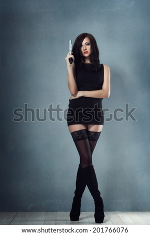 sexy brunette girl in a black dress and stockings boots holding a gun  - stock photo