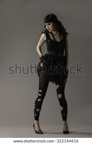 Sexy brunette girl in edgy outfit lifting her skirt slightly over her hip - stock photo