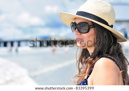 Sexy brunette girl with beach hat, summer dress and sunglasses staring in vain with the ocean reflection in her glasses - stock photo